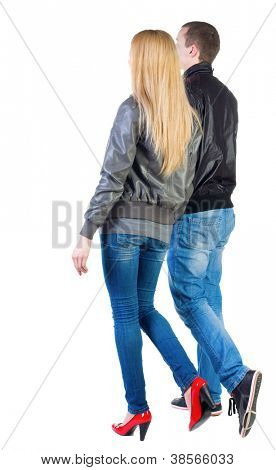 Back view of going young couple (man and woman) . walking girl and guy in jacket and jeans together. Rear view people collection.  backside view of person.  Isolated over white background.