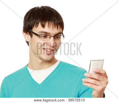 Closeup portrait of a happy young guy speaking on cellphone against white background