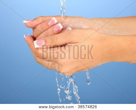 Washing woman's hands on blue background close-up