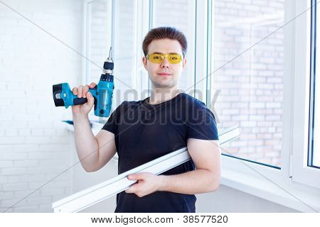 Man worker after installing new windows.