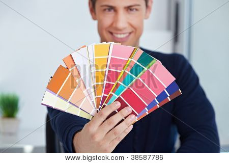 Happy graphic designer holding color fan in his hand