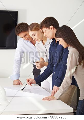 Architects team working on construction drawing in their office