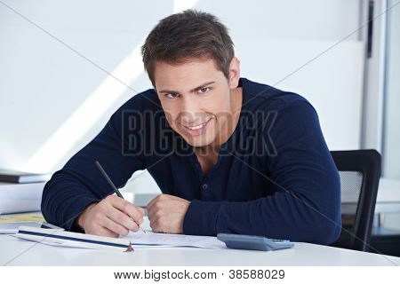 Architectural draftsman working at his desk in the office on a blueprint