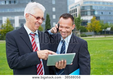 Two happy business men working outdoors with tablet computer and smartphone