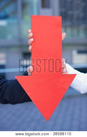 Hands holding a bold red arrow pointing down