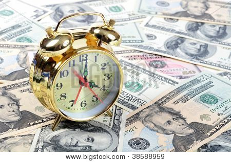 Alarm clock  for dollar banknotes close up