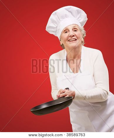 portrait of a friendly cook senior woman holding pan over red background