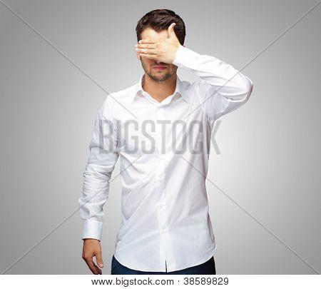 Retrato de um homem de negócios cobrindo olhos isolados em fundo cinza