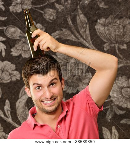 Portrait of a man holding bottle on head on background