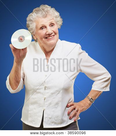 Senior woman holding cd isolated on blue background