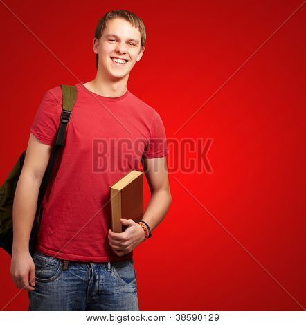portrait of young student holding book and carrying backpack over red