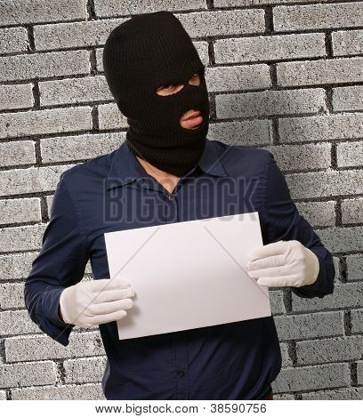 Man wearing a robber mask showing a blank paper, indoor