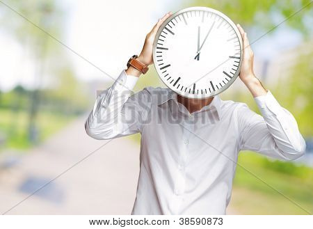 Young Man Holding Big Clock Covering His Face, Outdoor