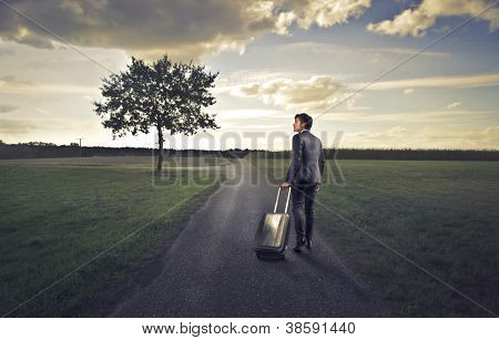 Businessman walking on a long countryside road with a luggage