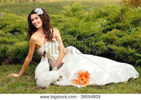 Novia joven sonriente jugando con lindo conejo sobre la naturaleza de verano parque al aire libre, Alice in Wonderl