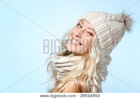 christmas girl, young beautiful smiling and give a wink over blue background