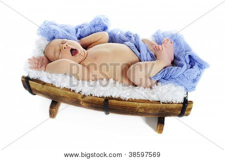 An adorable newborn on a fluffy white blanket in a half barrel, yawning ans stretching.  On a white background.
