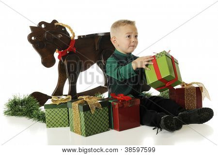 A young preschooler dressed up for Christmas, pleading for help with opening a gift.  On a white background.