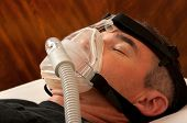 image of respiratory disease  - Man with sleeping apnea and CPAP machine - JPG