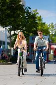 Couple - man and woman - riding their bikes or bicycles in their free time and having fun on a sunny