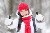 stock photo of vivacious  - Happy young Asian woman with a beautiful vivacious smile dressed warmly in winter clothes standing outdoors in a snowstorm giving thumbs up gesture of approval - JPG