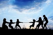 stock photo of pulling  - Kids playing tug war pulling rope - JPG