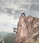 picture of rope pulling  - Businessman on the top of a rock helping an other businessman to climb it - JPG
