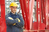 stock photo of millwright  - builder worker in uniform and safety protective equipment at construction site in front of metal construction frames - JPG