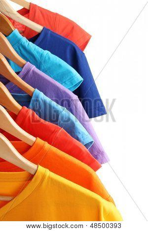 Montón de camisetas en perchas aislados en blanco