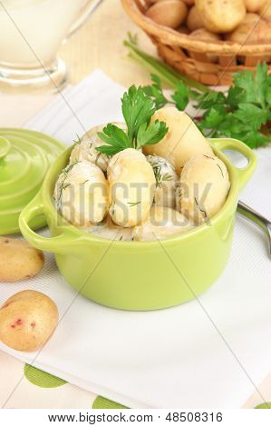 Tender young potatoes with sour cream and herbs in pan on wooden table close-up