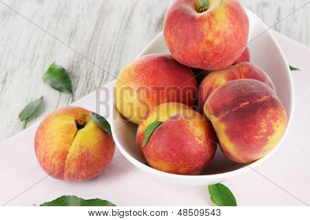 Peaches in plate on napkin on wooden table