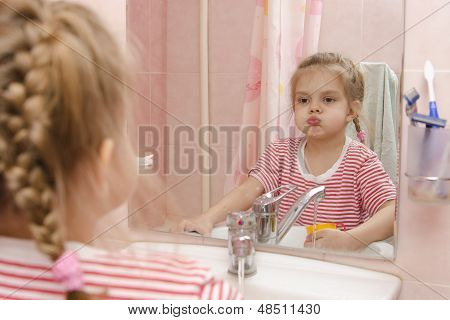 Four-year-old girl rinse teeth after cleaning in the bathroom