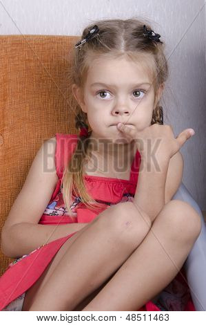 Girl sitting on the couch and thoughtfully looks to the left