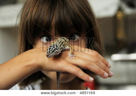 Humourous Picture Of Cross-eyed Child Holding A Gecko