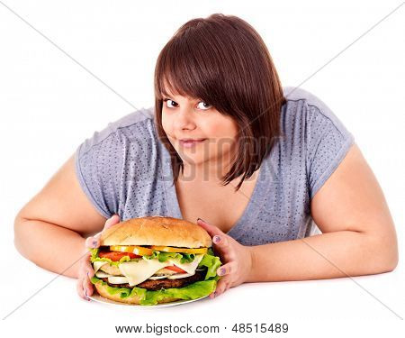 Overweight woman holding big hamburger.