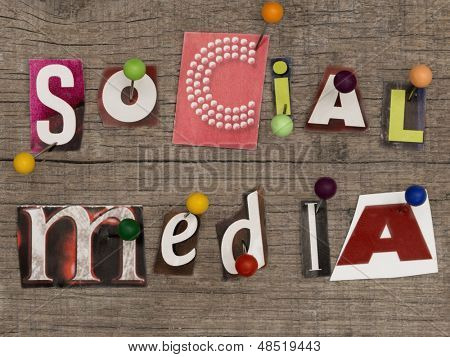 title SOCIAL MEDIA  made of letters from newspapers with pins on the wooden background