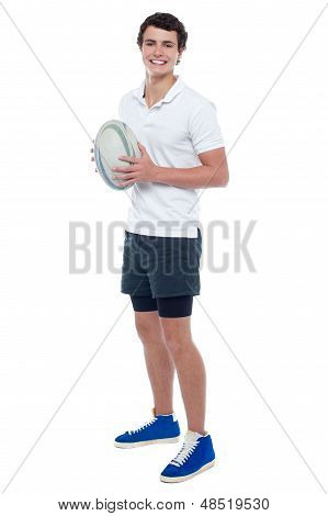 Full Length Portrait Of A Rugby Player Holding Ball