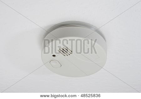 a smoke detector on a white ceiling