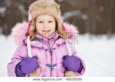 Half-length portrait of smiling little girl in pinky jacket with fur collar and earflapped hat in winter park