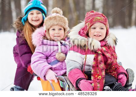 Laughing older girl pushes sledgesin which two younger girls sit, focus on first girl