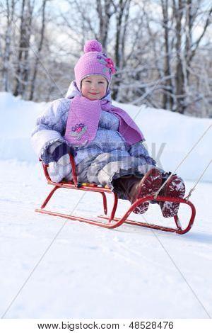 Happy little girl in pink scarf and hat goes tobogganing on snow in winter.