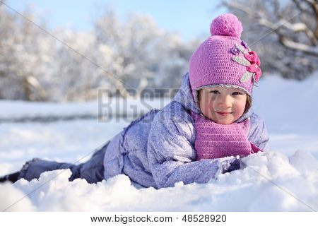 Warmly dressed little happy girl in pink scarf and hat lies on snow in winter.