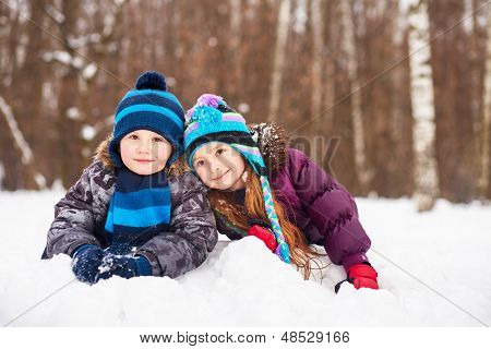 Little girl and boy lie nearby on snowdrift in winter park