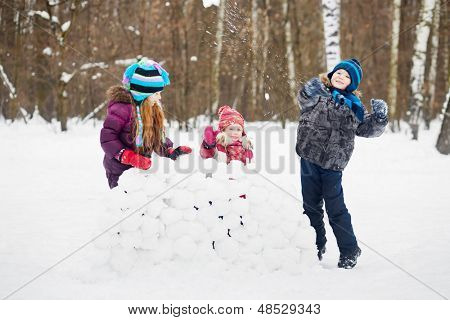 Two girl stands behind wall made of snow blocks and boy throws snowball