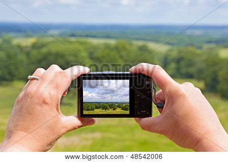 A woman using the rear lcd screen to compose and take a landscape photo with her compact digital camera using liveview.