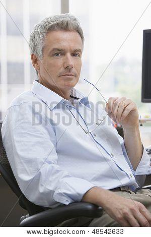 Closeup portrait of a serious mature businessman sitting at office desk