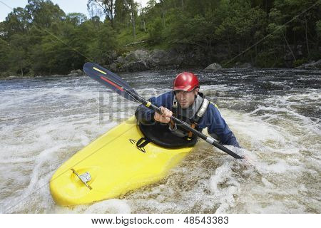 View of a young man kayaking in river