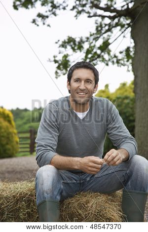 Thoughtful smiling man sitting on haybale in the field
