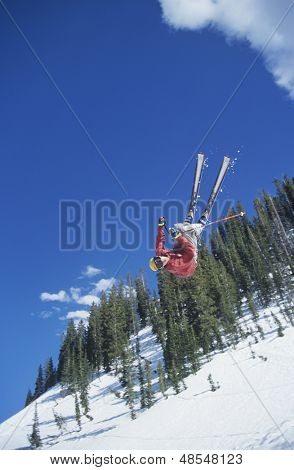 Person on skis jumping against trees and blue sky