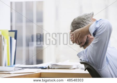 Closeup side view of a businessman with hands behind head in office